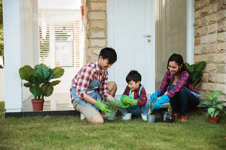 children planting trees with parents